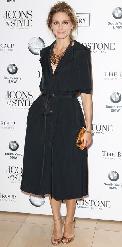 Olivia Palermo took her front row seat at a fashion show in Melbourne in a voluminous black ladylike shirtdress that she paired with metallic gold accessories.
