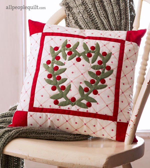 The delightful pillow shows a love of traditional needle-turn appliqué.