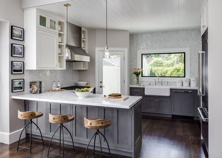 Gray and white marble tiles laid in a herringbone pattern extend far beyond the traditional backsplash area to add graphic interest to the kitchen's back wall.