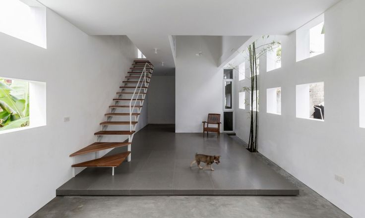 Nguyen Khac Phuoc Architects slots a skinny and light-filled four-meter-wide townhouse into the city of Vinh, Vietnam.