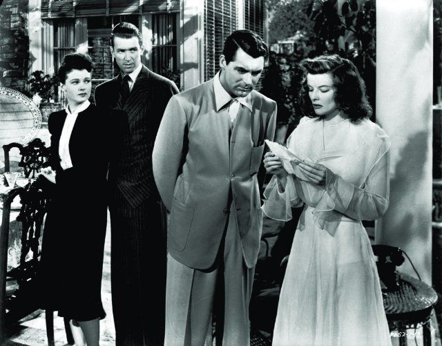 Still of Cary Grant, Katharine Hepburn, James Stewart and Ruth Hussey in The Philadelphia Story (1940).  Grant wears clean and simple lines.  Stewart in a pinstripe suit with wide lapels.