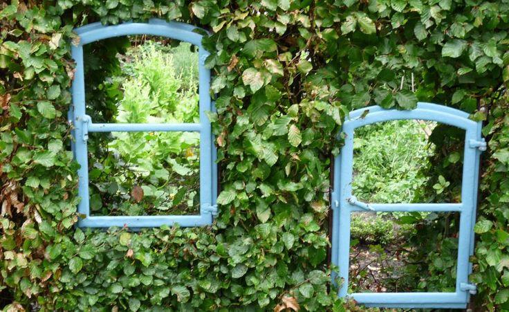 Zwei in die Buchenhecke eingesetzte Fensterrahmen gewähren einen Einblick in den benachbarten Gartenraum