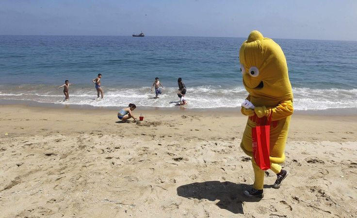 A man dressed in a condom costume walks at Caleta Portales beach, during a summer awareness campaign by the Chilean Corporation for the Prevention of AIDS in Valparaiso city, northwest of Santiago January 9, 2015. (Photo by Rodrigo Garrido/Reuters)