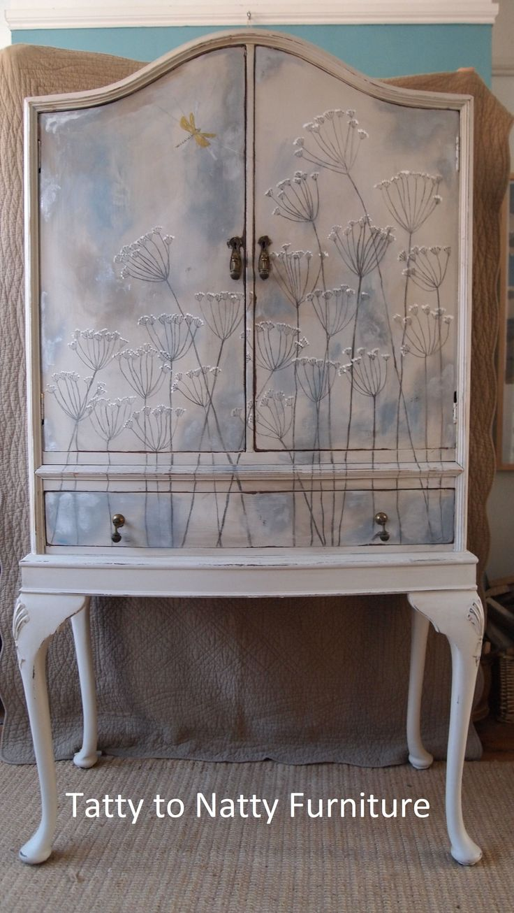 Painted tallboy cabinet in greys blues and metallic gilding waxes in silver and blue pearl. Decorated in a hand drawn cow parsley design in graphite and white and a gold dragonfly. Find me on facebook (link in bio) for current projects and commissions.