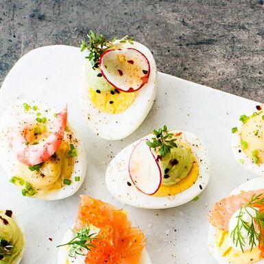 """Ägg och avokado är """"a match made in heaven"""", som det heter på engelska. Här gör vi kräm på avokadon och spritsar på ägghalvor. Toppa med skivade rädisor, chiliflakes, svarta sesamfrön och smörgåskrasse – vackert! Perfekt på midsommarbuffén."""