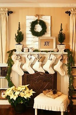 Vintage-y Christmas mantle- the white-washed pallet wood behind the wreath- perfect.