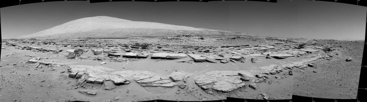 This landscape scene photographed by NASA's Curiosity Mars rover shows rows of rocks in the foreground and Mount Sharp on the horizon.