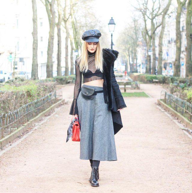Una falda midi en gris con volantes y adornada especialmente de forma muy moderna con una bandolera, se une a una bellísima blusa de tejido transparente y mangas adornadas con volantes.