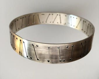 A bangle hand cut from sterling silver.