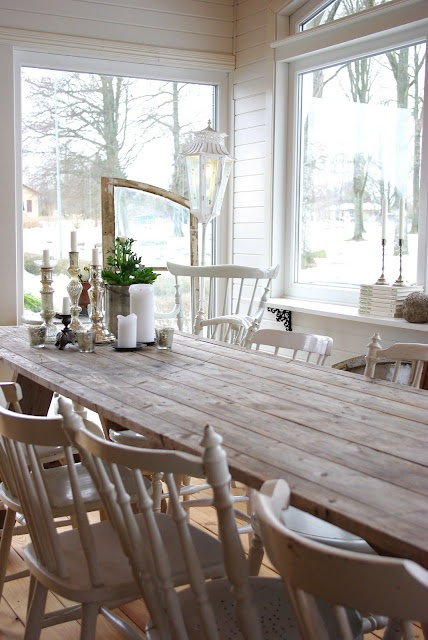 Another big dining table.  I also love the abundance of light and windows here, and how the mismatched chairs are all painted white to unify them.