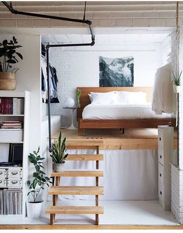 white and wood bed on a platform, wooden steps, plants, white brick, white shelves, wooden bed frame