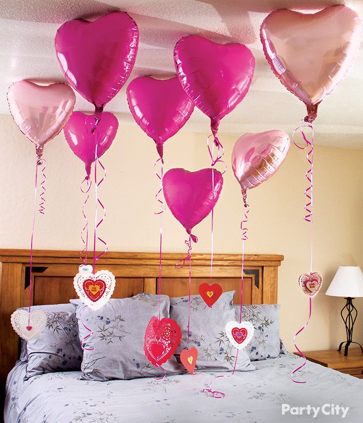 Surprise your loved one with this sweet Valentine's Day balloon surprise! Tie a ribbon to each balloon, curl the end and then add a thoughtful message on the paper doily.