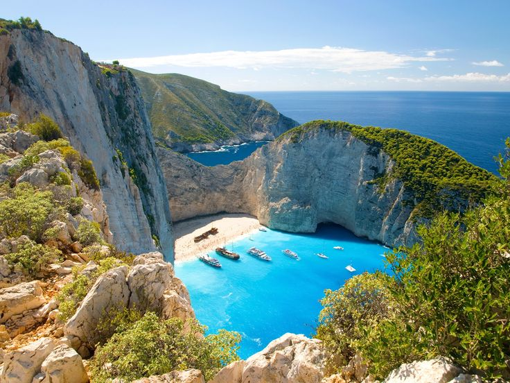 """Why we love it: Sheltered by cliffs, Navagio is only accessible by boat, and draws its name (""""Shipwreck"""") from a freighter that ran aground, was abandoned, and still rests in the beach's white sands today."""