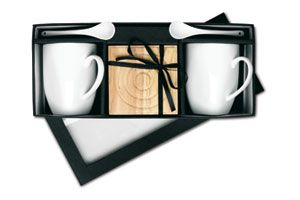 Set de dos tazas de café y cucharillas de porcelana con platos de madera.