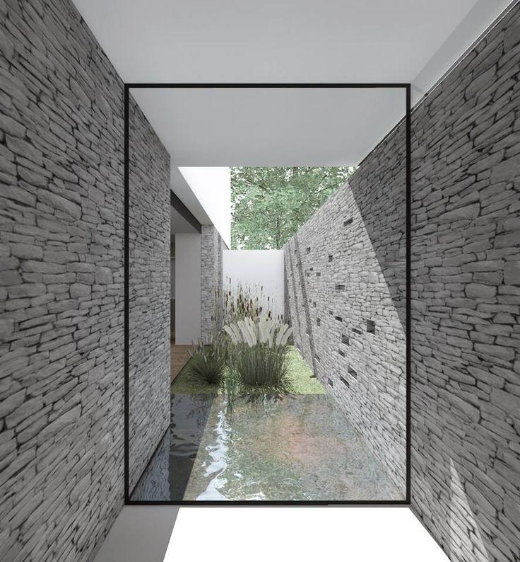 Le sas d'entrée avec une perspective sur le patio végétalisé et lumineux qui apparaît entre les deux murs.