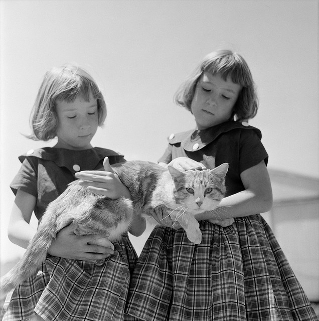 Douglas Jones: farm girls with cat, Iowa, 1958    Iowa farm girls, dressed identically, holding a cat. Photograph by Douglas Jones on assignment for LOOK magazine, 1958.