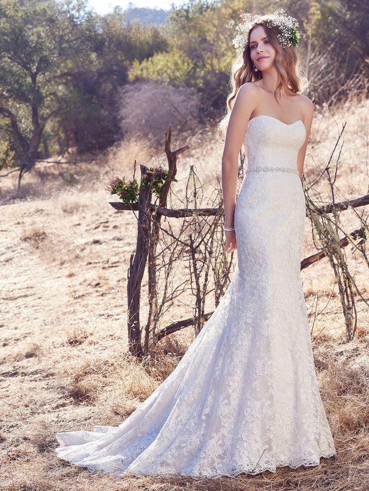 Maggie Sottero - JASLYNN, Exquisite lace appliqués add sweet glamour to this strapless sheath wedding dress, complete with a soft scoop neckline. Lined with shapewear underlay for a figure-flattering fit. Finished with covered buttons over zipper closure. Beaded belt on grosgrain ribbon sold separately.