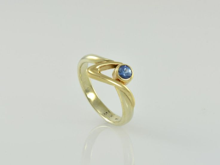 """-Vancouver- NZ$1099-  9ct Gold with Sapphire. This contemporary ring in 9ct white gold band is enhanced with a yellow gold """"V shape"""" at the top. It draws your eye to the ocean blue sapphire set in a rub-over setting. Enjoy wearing this comfortable, modern ring. Ring width top 10mm, bottom 3mm, ring size O, blue sapphire - 4mm. Jewellery made @jewelbeetle in Nelson, New Zealand."""