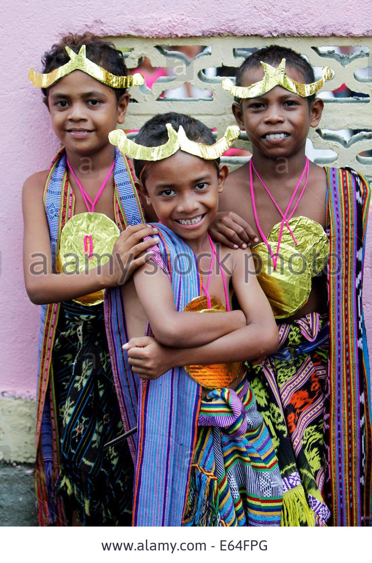 Children in traditional clothes and golden paper headdresses and medals during a festival. Dili, East Timor (Timor Leste)