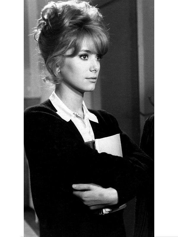 1962年の短編集『パリジェンヌ』で、パリの女学生を演じたドヌーヴ。白いシャツにカーディガンというシンプルな出で立ちにに、ドラマチックなアップヘアを合わせて。