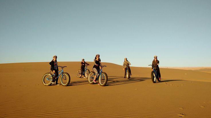 Girls fat biking at Atacama Desert sand dunes, Chile.  Altos de Pica sand dune field, Tarapacá region. Come on ride with us!