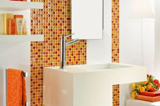mosaïque murale en orange et rouge dans la salle de bains blanche