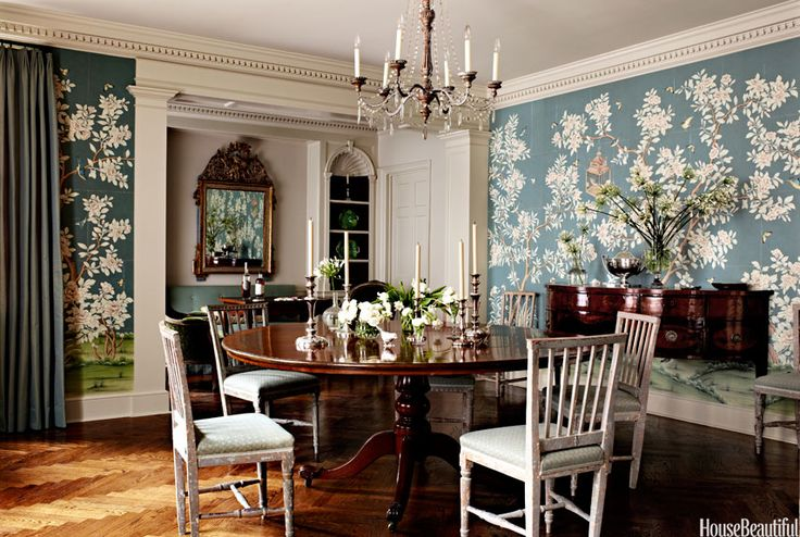 """Designer Suzanne Rheinstein brought a New York City dining room to life with a vibrant, scenic Chinese wallpaper by Gracie. She and the young homeowners chose fine furnishings """"that will see them through their lives,"""" she says. Rheinstein loves painted pieces against rich, dark woods, so she paired chalky Gustavian dining chairs with an antique English mahogany table.   - HouseBeautiful.com"""