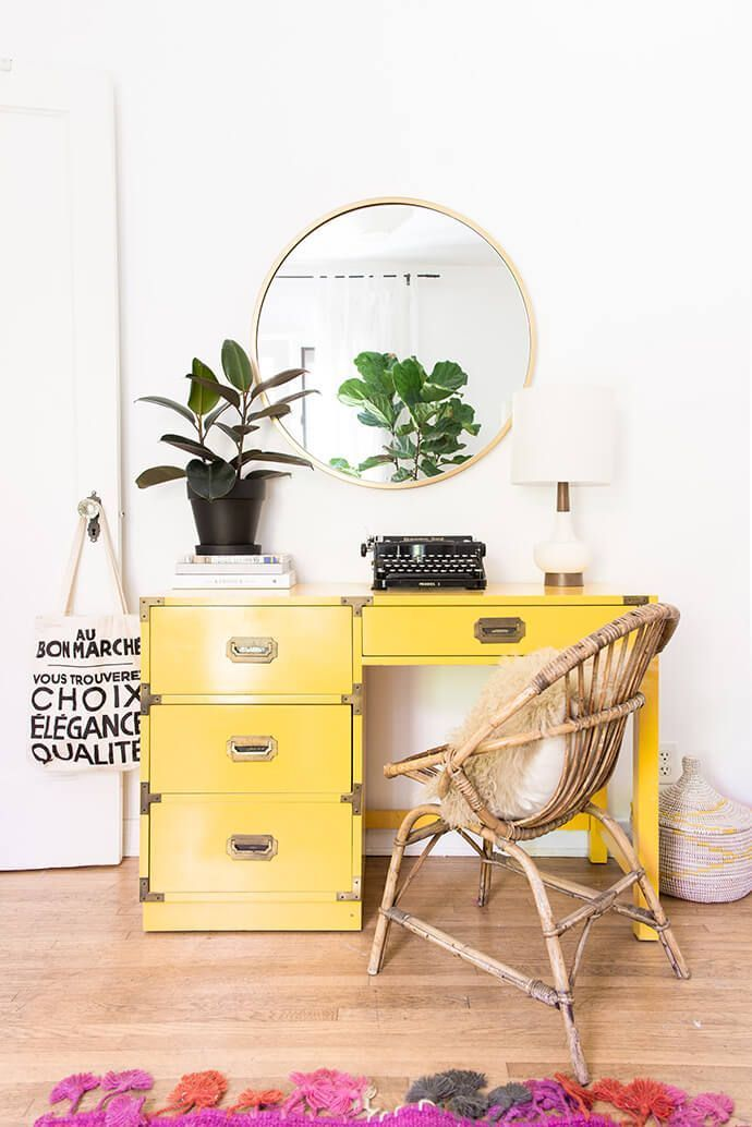 Bedroom with a workspace with a yellow desk, circle mirror, and a wooden chair