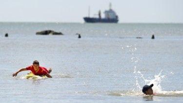 PÅ VAKT: En livvakt patruljerer stranden på et surfebrett i Saint-Nazaire i Frankrike. Foto: Jean-Sebastien Evrard/AFP