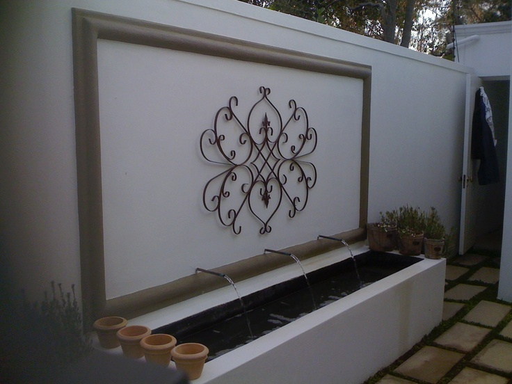 Water feature, cement corbel (frame) and wrought iron detail by Garden Bleu