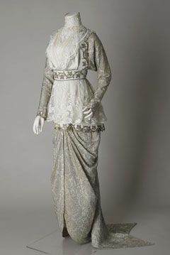 Wedding dress, 1913. In the style of Paul Poiret. Batwing-shaped sleeves and draped skirt with fishtail train are silk and gold thread brocade. Main bodice is cream wool cashmere, edged with border of embroidered gold thread, with a high-necked overbodice of machine-made lace on a net ground. Cashmere waistband is embroidered with gold metallic thread. The bride also wore a large black velvet picture hat with wide brim and ostrich feather trim.