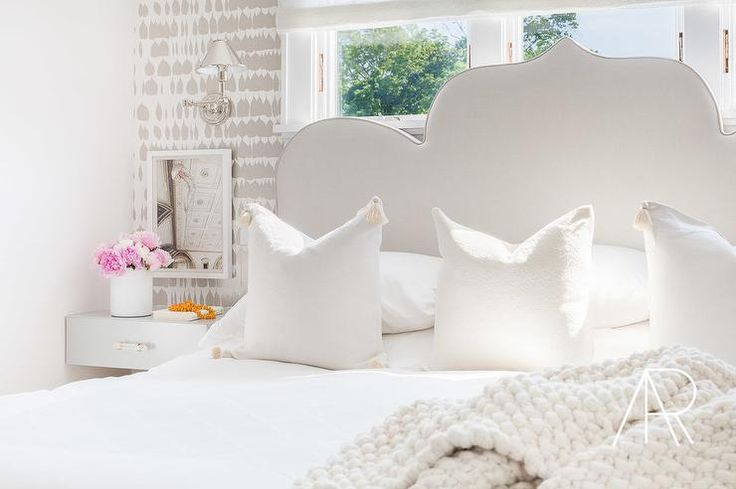 Alyssa Rosenheck - Raquel Garcia Design - White tassel pillows sit atop a Moorish style bed, dressed in white bedding and placed in front of a window framed by Queen of Spain Wallpaper.