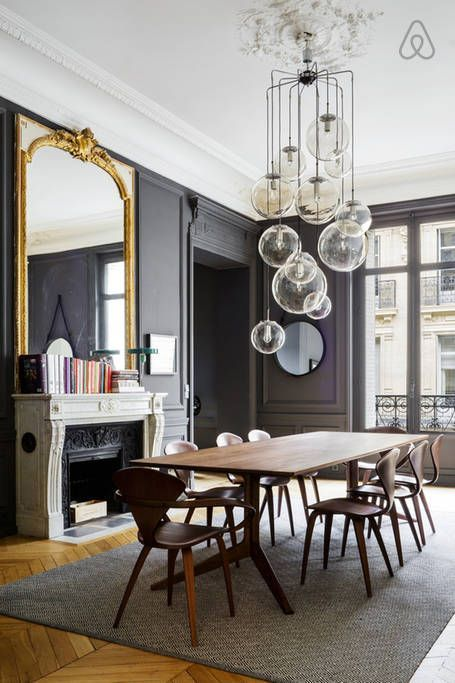 The perfect Parisian apartment! Dark walls, oversized gold framed mirror, gorgeous light fixture, dining table and chairs