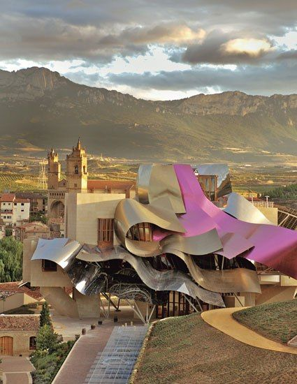 Frank Gehry's Hotel Marqués De Riscal, in La Rioja, sits in the shadow of Elciego's medieval Church of San Andrés and of the Sierra de Cantabria; the Valdez-caray Range is to the hotel's southwest.