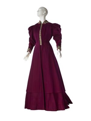 House of Worth. c.1900  Orchid wool broadcloth; magenta velvet; cream silk floss, cream chenille yarn on pale blue velvet embroidered in octagonal motifs, gold metallic spokes in centers; gilt embroidery; white silk floral damask; purple taffetaA) Jacket: Princess line, jacket and vest effect; calf-length;gigot sleeves, puffed/box-pleated upper arm to elbow, fitted to wrist, B) Skirt: Trumpet-shaped, floor-length, slight train.