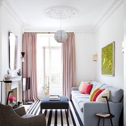 March 2015 UK House&Garden. Small living spaces. How to expand a narrow living room? In this Notting Hill town house, interior designer Suzy Hoodless used strong, clean lines to emphasise the high ceilings, softened by a bespoke George Smith sofa and colourful cushions. When space is limited, it can be tempting to mount the television to the wall, but here it is unobtrusively tucked to the side to ensure the frameless mirror (also space-enhancing) is a focal point.