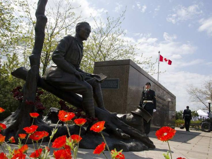 Poppies surround the newly unveiled statue of Lt.-Col. John McCrae to commemorate the Second Battle of Ypres and his poem In Flanders Fields during a ceremony in Ottawa on Sunday, May 3, 2015.