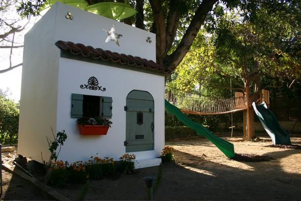 With Spanish tiles, flat roof and custom door, this playhouse is a miniature version of the family home.
