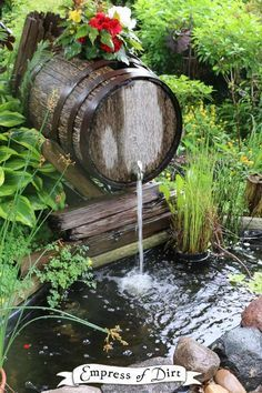 Wooden barrel waterfall over a backyard garden pond