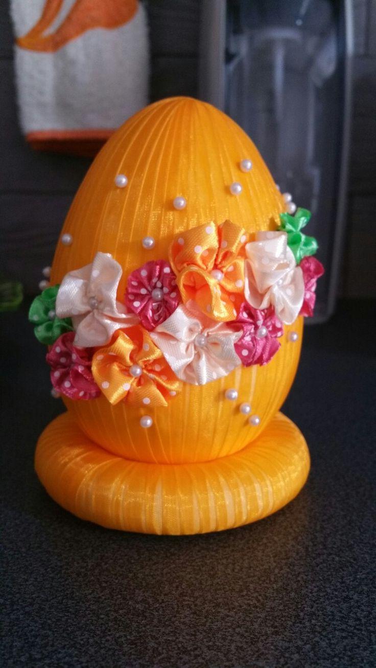 Uovo polisterilo decorato con nastrino arancione, fiori variopinti e perline bianche