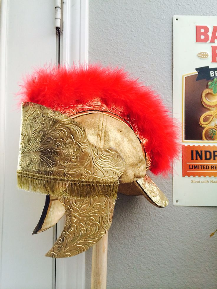 Roman soldier helmet made out of a baseball cap, cardboard, feather boa, styrofoam plates, embossed vinyl fabric, and fringe.