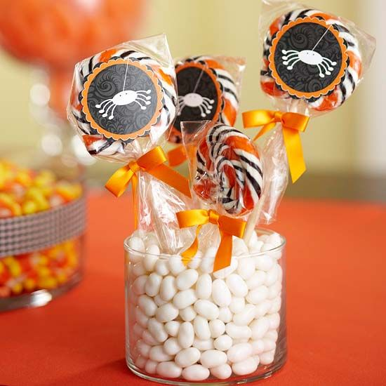 Halloween Sucker Centerpiece  Take cellophane-wrapped pops and add decoration. Display in clear glass filled with white jelly beans.