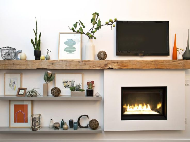Make a new addition look like an always-been-there architectural element by surrounding it with built-in shelves. Designer Mary Jo Fiorella tops this modern gas fireplace with a long, rustic wood mantel and flanks it with floating shelves to provide plenty of display space.