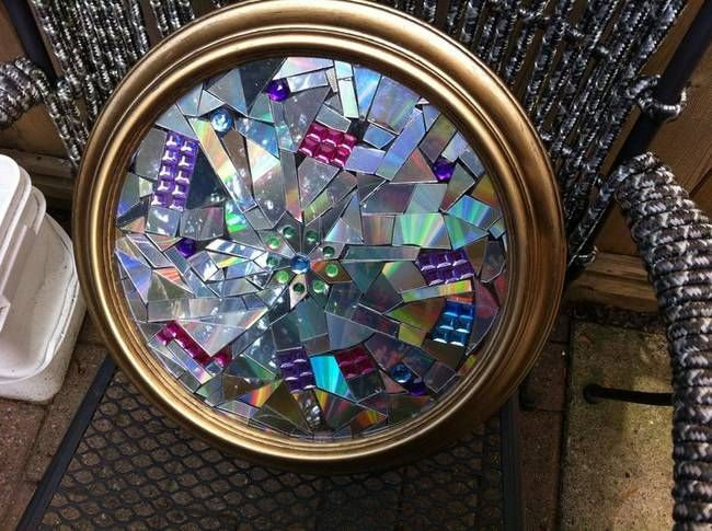 7a) Wall Art - A decorative mosaic piece can brighten up any dull room. Just take an old frame, glue pieces of old CDs to it, and hang it up