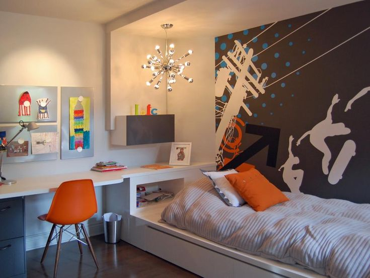 A sleek white built-in bed and desk feature lots of storage space. A skateboard-themed mural ties in the room's orange and blue accent colors, and a modern silver chandelier highlights the bed area.