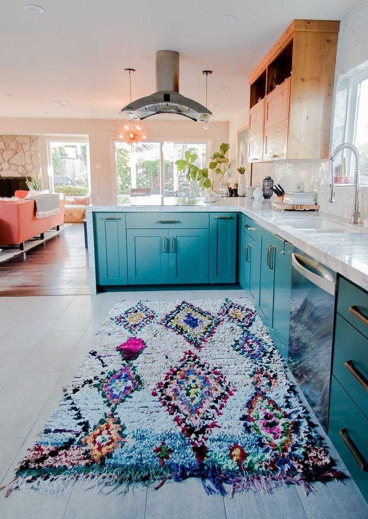 Pretty range hood, blue cabinets and colorful rug