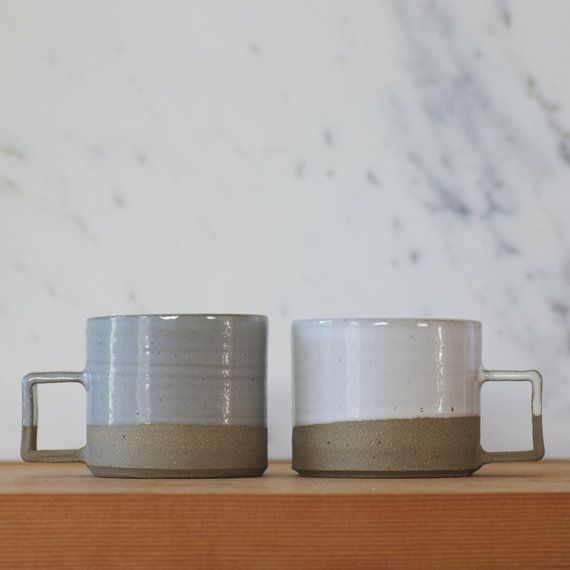 Two mugs. These are made of sand colored stoneware clay with french grey and white glaze. These are two seconds from a large custom order I made