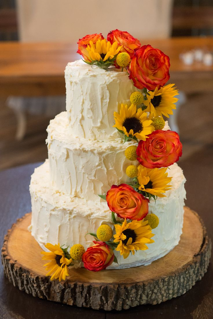 Wedding cake. This cake, made by the bride's uncles, contained layers of chocolate, coconut and pumpkin, sure to please any palate. The cascading flowers matched the circus roses on the groomsmen's boutonnieres and the sunflowers mimics those in the brides bouquets. The wooden cake stand was made by the father of the bride.
