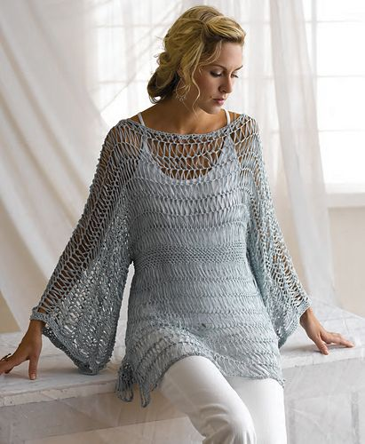 This tunic sweater is almost completely crocheted with hairpin lace, a very stretchy, open fabric of strips that are joined as you go. There is a solid single crochet waistband, lending structure to the tunic and loosely defining the waist. The unique texture of the flat ribbon yarn is prominently displayed by the open construction, and the simple repetitive stitch pattern creates a clean look for the finished garment. With a relaxed fit and airy but elegant appearance, this is a truly…