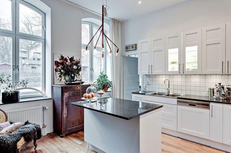 Kök från Ballingslöv med mycket god förvaring bakom vita luckor. Praktisk bänkbelysning samt kakel ovan påkostade stenskivor. Köksö erbjuder kompletterande förvaring/arbetsyta.